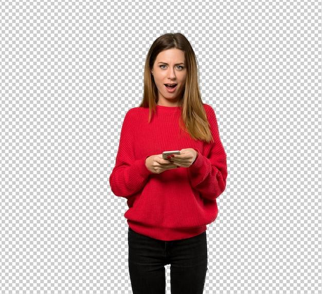 Junge frau mit roter strickjacke überrascht und eine mitteilung sendend