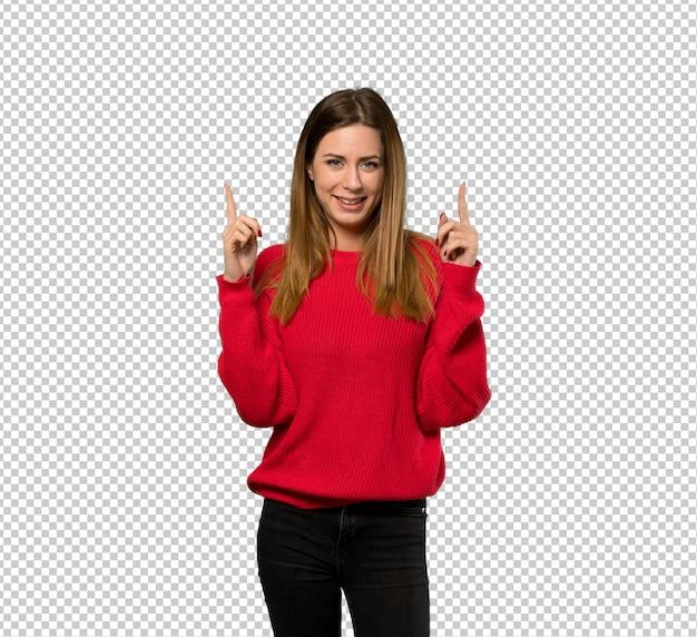 Junge frau mit roter strickjacke zeigend mit dem zeigefinger eine großartige idee