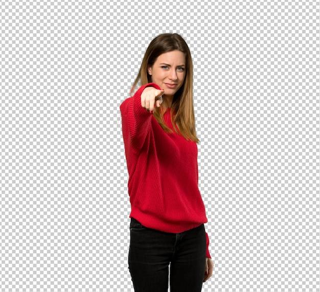 Junge frau mit roter strickjacke zeigt finger auf sie mit einem überzeugten ausdruck