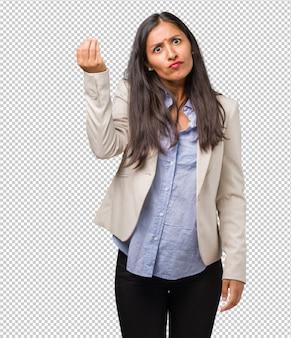 Junge geschäftsindische frau, die eine typische italienische geste tut, lächelt und geradeaus schaut, symbol oder ausdruck mit hand