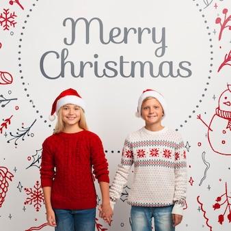 Junge geschwister des modells mit weihnachtsstrickjacken