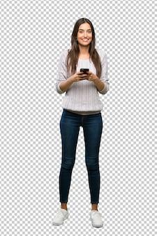 Junge hispanische brunettefrau, die eine mitteilung mit dem mobile sendet
