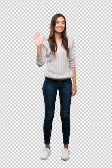 Junge hispanische brunettefrau, die mit der hand mit glücklichem ausdruck begrüßt