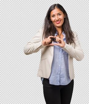 Junge indische geschäftsfrau, die ein herz mit den händen macht