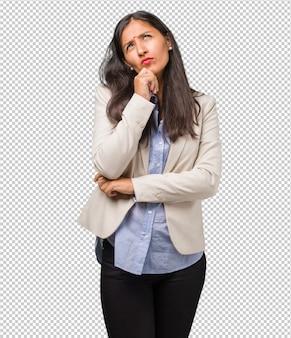 Junge indische geschäftsfrau, die oben denkt und schaut