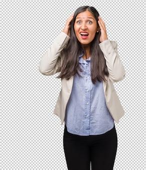 Junge indische geschäftsfrau frustriert und hoffnungslos, verärgert und traurig mit den händen auf kopf