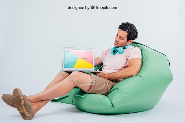 Junge kerl sitzt mit kopfhörer und laptop mock up