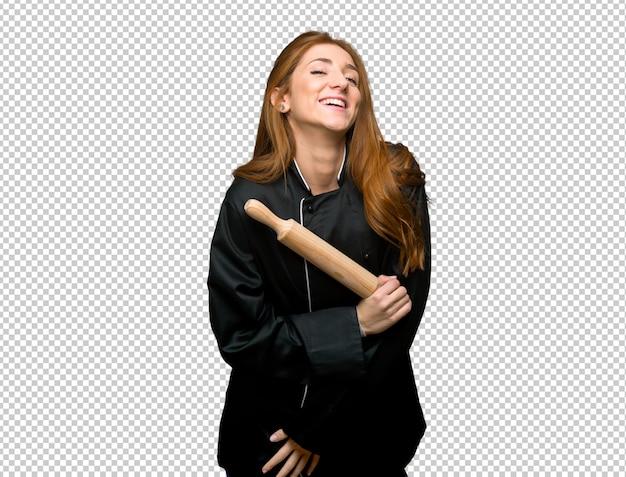 Junge lächelnde rothaarigecheffrau beim setzen von händen auf kasten