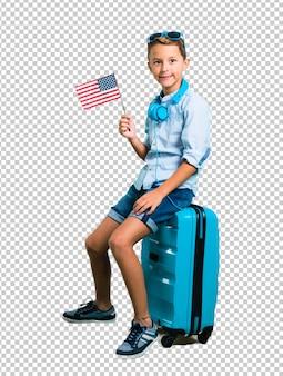 Junge mit der sonnenbrille und kopfhörern, die mit seinem koffer hält eine amerikanische flagge reisen