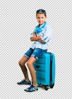 Junge mit der sonnenbrille und kopfhörern, die mit seinem koffer mit seinen gekreuzten armen reisen