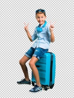 Junge mit der sonnenbrille und kopfhörern, die mit seinem koffer reisen, der sieggeste macht