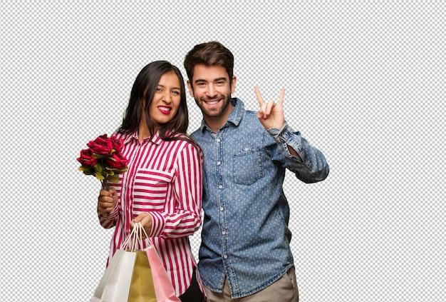 Junge paare am valentinsgrußtag, der eine felsengeste tut