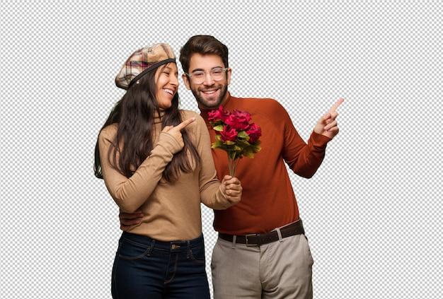 Junge paare am valentinsgrußtag lächelnd und zeigen auf die seite
