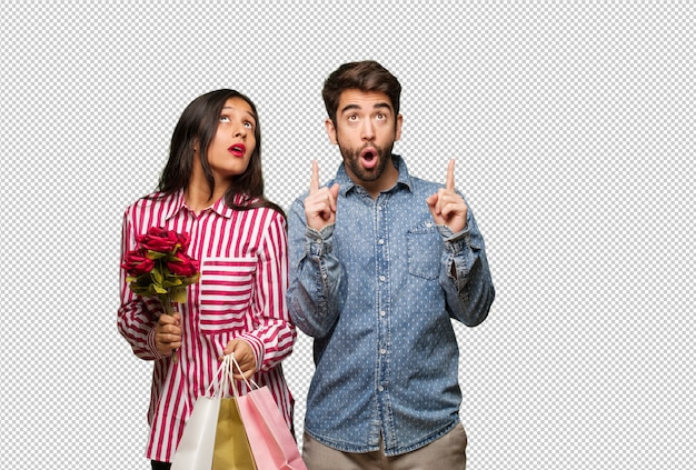 Junge paare am valentinsgrußtag überraschten oben zeigen, um etwas zu zeigen