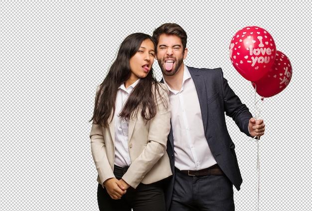 Junge paare im valentinsgrußtag funnny und freundliche darstellende zunge