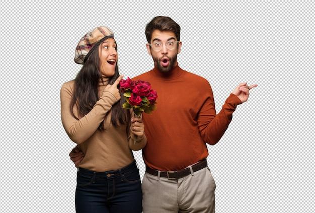 Junge paare im valentinsgrußtag zeigend auf die seite