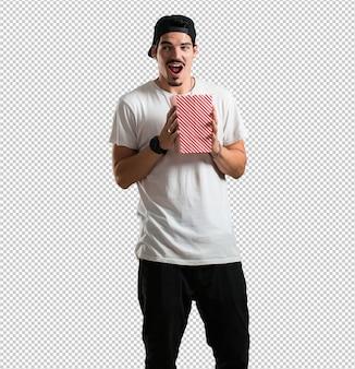 Junge rapper mann glücklich und fasziniert, hält einen gestreiften popcorn-eimer, überrascht von dem neuen film, die augen offen und ausdruck der bewunderung