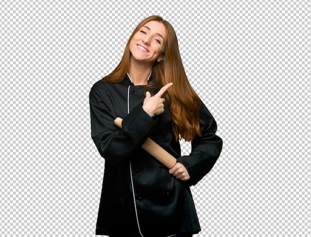 Junge rothaarigecheffrau, die auf die seite zeigt, um ein produkt darzustellen