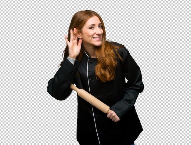 Junge rothaarigecheffrau, die auf etwas hört, indem sie hand auf das ohr setzt