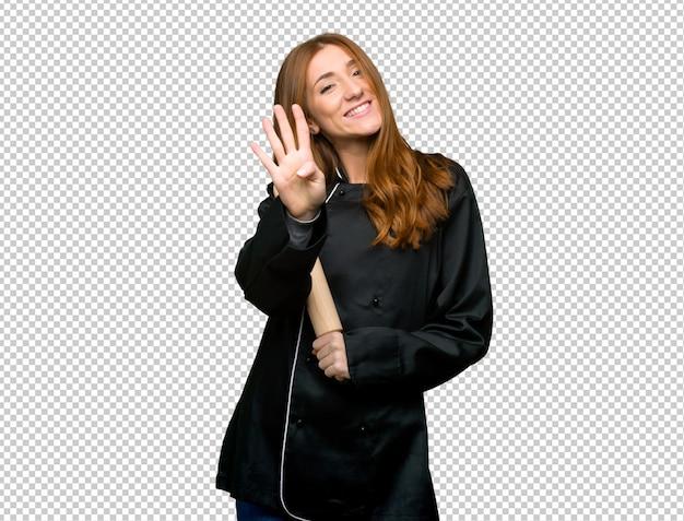 Junge rothaarigecheffrau, die vier mit den fingern glücklich und gezählt worden sein würden