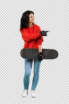 Junge schlittschuhläuferfrau, die auf die seite zeigt, um ein produkt darzustellen