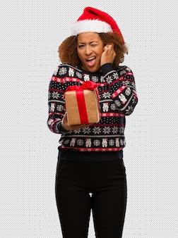 Junge schwarze frau, die ein geschenk in den weihnachtstagbedeckungsohren mit den händen hält