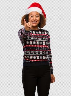 Junge schwarze frau in einer modischen weihnachtsstrickjacke mit dem druck, der eine felsengeste tut