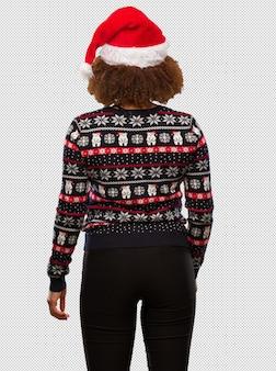 Junge schwarze frau in einer modischen weihnachtsstrickjacke mit druck von hinten, zurück schauend