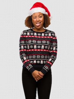 Junge schwarze frau in einer modischen weihnachtsstrickjacke mit funnny druck und freundlicher darstellender zunge
