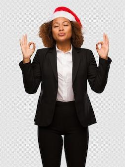 Junge schwarze geschäftsfrau, die einen weihnachts-sankt-hut durchführt yoga durchführt