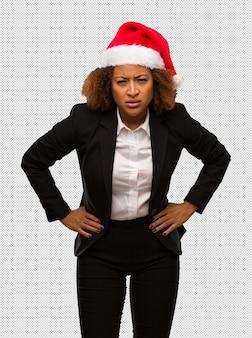 Junge schwarze geschäftsfrau, die einen weihnachtssankt-hut schimpft jemand sehr verärgert trägt