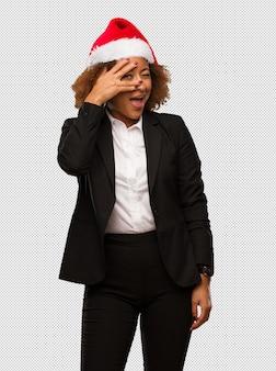 Junge schwarze geschäftsfrau, die einen weihnachtssankt-hut trägt, der gleichzeitig verlegen ist und lacht