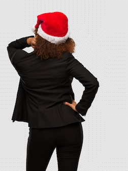 Junge schwarze geschäftsfrau, die einen weihnachtssankt-hut von hinten denkend an etwas trägt