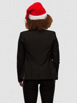 Junge schwarze geschäftsfrau, die einen weihnachtssankt-hut von hinten, zurück schauend trägt