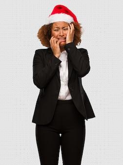 Junge schwarze geschäftsfrau, die einen weihnachtssankthut verzweifelt und traurig trägt