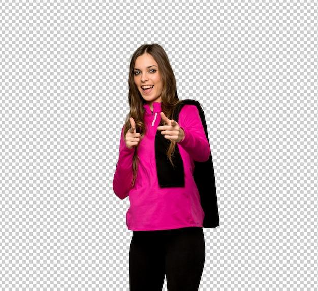 Junge sportfrau, die auf die front und das lächeln zeigt