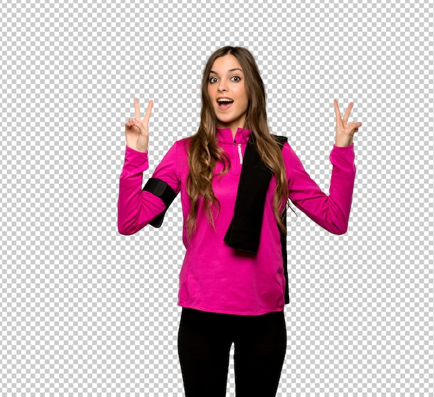 Junge sportfrau, die siegeszeichen mit beiden händen lächelt und zeigt