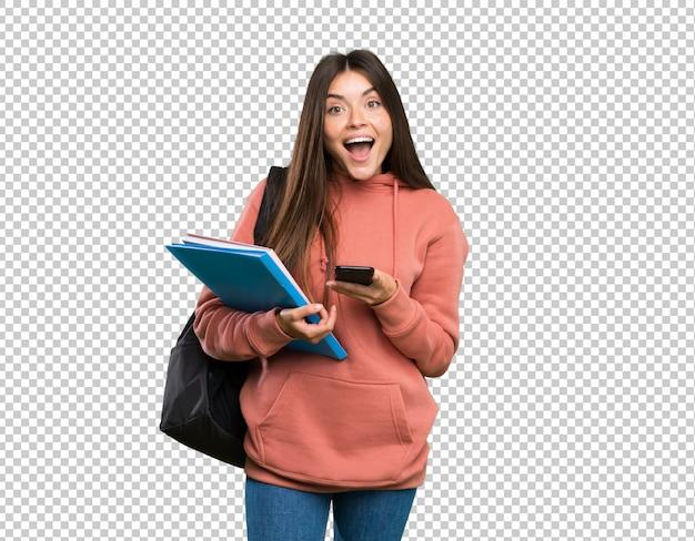 Junge studentenfrau, die notizbücher überrascht hält und eine mitteilung sendet