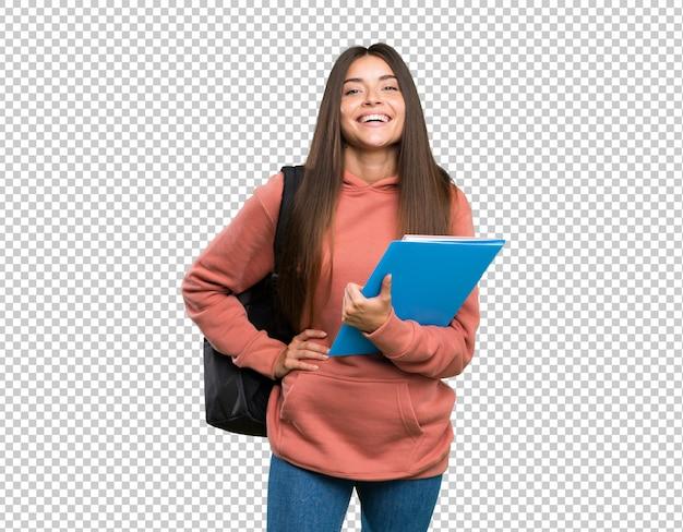 Junge studentenfrau, welche die notizbücher aufwerfen mit den armen an der hüfte und am lächeln hält