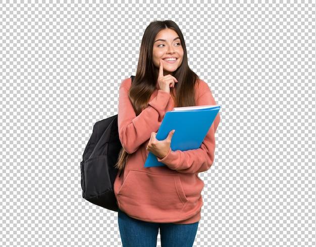 Junge studentenfrau, welche die notizbücher denken eine idee beim oben schauen hält