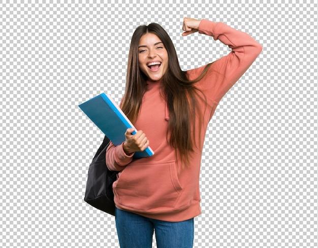 Junge studentenfrau, welche die notizbücher feiern einen sieg hält