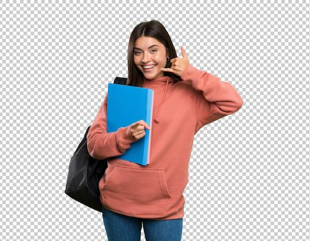 Junge studentenfrau, welche die notizbücher machen telefongeste und zeigen front hält