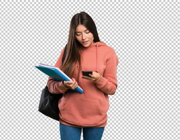 Junge studentenfrau, welche die notizbücher senden eine mitteilung mit dem mobile hält