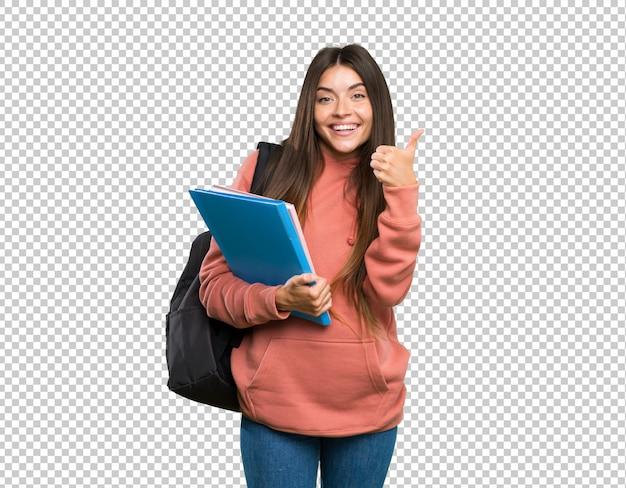 Junge studentenfrau, welche die notizbücher zeigen okayzeichen und daumen herauf geste hält