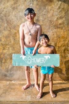 Jungen, die an einem swimmingpool duschen