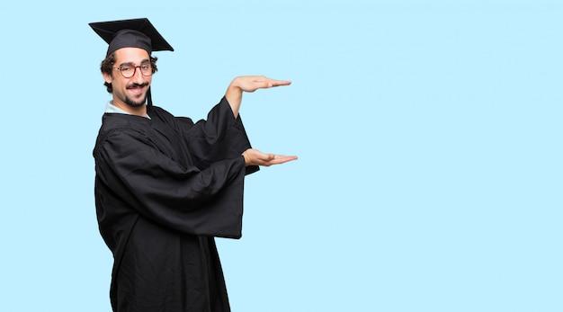 Junger abgestufter mann, der mit einem erfüllten ausdruck lächelt einen gegenstand oder ein konzept lächelt