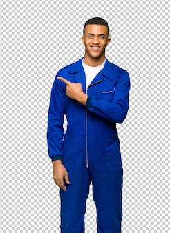 Junger afroamerikanischer arbeitskraftmann, der auf die seite zeigt, um ein produkt darzustellen