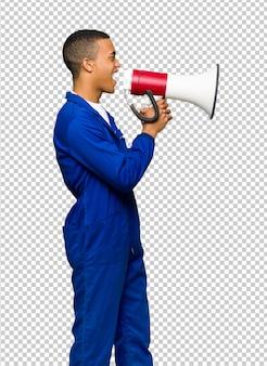 Junger afroamerikanischer arbeitskraftmann, der durch ein megaphon schreit, um etwas in seitlicher position anzukündigen
