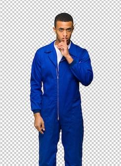 Junger afroamerikanischer arbeitskraftmann, der ein zeichen der ruhegeste finger in mund setzend zeigt
