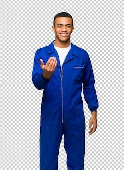 Junger afroamerikanischer arbeitskraftmann, der einlädt, mit der hand zu kommen. glücklich, dass du gekommen bist
